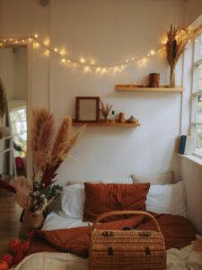 Gemütlich dekoriertes Schlafzimmer mit Blick auf das Bett und Lichterketten